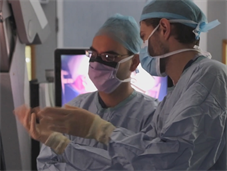 Two neurosurgeons in PPE discussing a scan