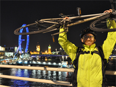 Cyclist holding up bike in front of London skyline