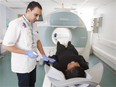Radiographer prepares patient on scanner bed for nuclear medicine scan
