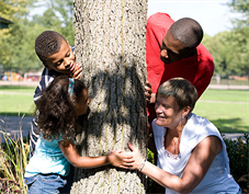 Family group around a tree in a park