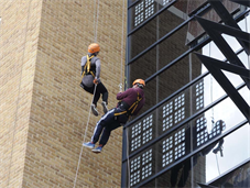 Two people abseiling down the side of Golden Jubilee Wing