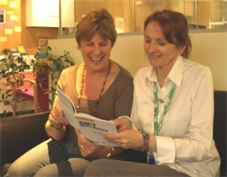 Two women reading diet and cancer leaflet