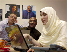 3 colleagues looking at laptop